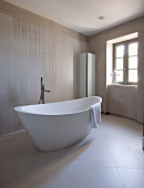 Free-standing designer bathtub and standpipe tap fitting in modern bathroom with pale tiles on walls and floor