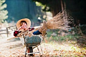 Woman with besom broom sitting in wheelbarrow of autumn leaves in garden