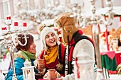 Two women and one man talking at a Christmas market