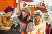 Two women and one man warming themselves around fire at Christmas market