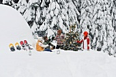 Young people sitting below Christmas tree in snow