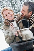Couple sitting by camping stove in snow drinking tee