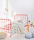 White bed linen with multicoloured polka-dots on orange metal bed in bedroom flooded with light
