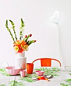 Dining area in cheerful colours with bright orange, retro chair and amusing, heart-shaped lamp