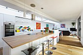 Kitchen counter with pale wood worksurface and bar stools in open-plan interior