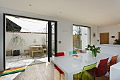 Colourful plastic chairs around white dining room in front of open terrace doors with view of courtyard