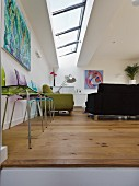 Colourful plastic chairs against wall and sofa set below skylights in living room