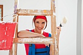 Woman holding paint brush leaning on ladder