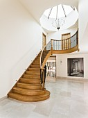 Skylight above curved wooden staircase in large foyer