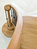 Solid oak staircase with curved bannister rail, spiral newel post and wrought iron balusters