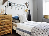 Wooden chest of drawers next to bed with striped bed linen below bunting on wall