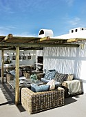 Mediterranean holiday home with rattan furniture below pergola on terrace