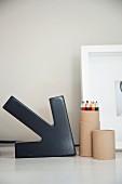 Schwarzer Pfeil (Kunstobjekt) und Stiftebox auf Schreibtisch