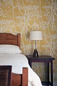 Holzbett und Lampe auf Nachttisch vor Tapete mit floraler Muster