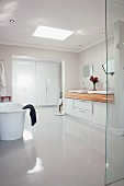 Purist ensuite bathroom with polished white floor and wooden washstand counter