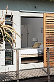 View into bedroom from wooden terrace through open sliding shutters