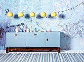 Row of yellow pendant lamps above sideboard painted pale blue on wooden base frame in front of wall with crumbling plaster
