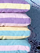 Stack of cushions with striped covers in different pastel shades