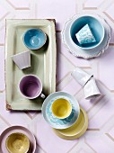 Top view of cups in pastel shades, some on dishes and saucers on patterned, retro tablecloth