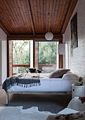 Bed with chrome metal frame against wall in front of terrace doors in plain bedroom with wooden ceiling