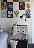 Detail of bedroom with modern stool in front of vintage bedside table against wall below collection of posters