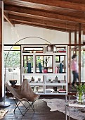 Arc lamp above butterfly armchair in front of shelving in lounge area with glass walls