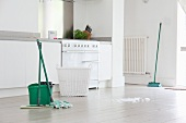 Mops and bucket on white floor in kitchen