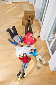 Family lying on floor of empty living room
