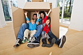Family sitting in large packing case in empty living room