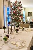Dezent gemusterte Tischdecke mit Servietten und Rosendeko auf festlicher Tafel mit Weihnachtsbaum im Hintergrund