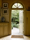 View into garden through wood and glass door opened outwards; stylish country house kitchen in soft, Shaker beige