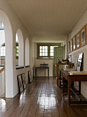 Framed pictures hung and leaning on walls of gallery with historic arched apertures running around open stairwell