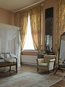 High-ceilinged bedroom with gathered curtains and walls painted in pastel pink and apricot; antique armchair and four-poster bed with white voile canopy