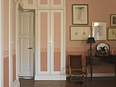 Interior door surrounded by fitted wardrobes in stylish bedroom; walls and wardrobe doors in pastel pink with continuous border
