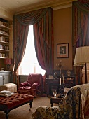 Comfortable armchairs with loose covers, ottoman and draped curtains with tassels in high-ceilinged salon of historic country house
