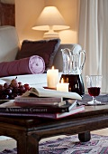 Books, grapes, candles and red wine on coffee table