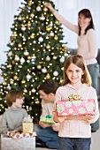 Girl holding Christmas gift in front of family