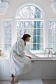 Woman in robe drawing bath