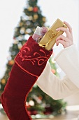 Woman stuffing gifts into Christmas stocking