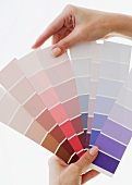 Close up of woman comparing paint swatches