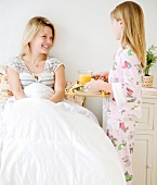 Daughter bringing mother breakfast in bed