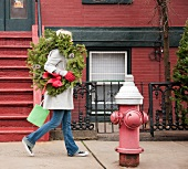 Woman carrying Christmas wreath on urban street