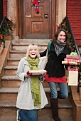 Women carrying Christmas gifts on front stoop