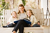 Mother reading to daughters on porch swing