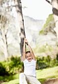 Girl (10-11) swinging on rope
