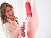 Woman painting wall with rollerpaint