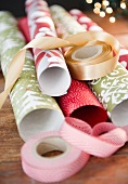 Mehrere Rollen weihnachtliches Geschenkpapier & Geschenkbänder