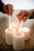 Close up of man's and woman's hands igniting candles