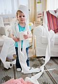 Girl (2-3) wrapped with toilet paper standing in living room