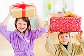 Girl (8-9) and boy (6-7) carrying christmas gifts on their heads